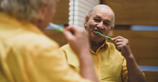 Elderly gentleman with dementia brushing teeth in mirror